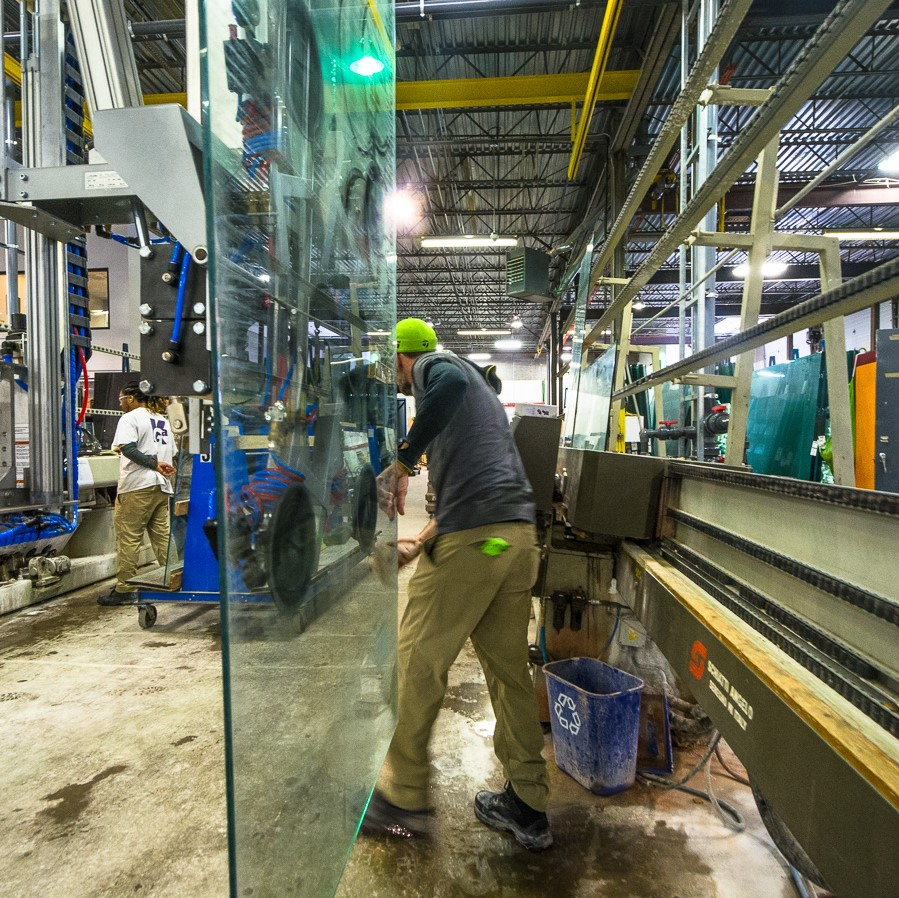 A worker in our fabrication facility worker moving a large piece of glass. A recycling bin sits next to him.