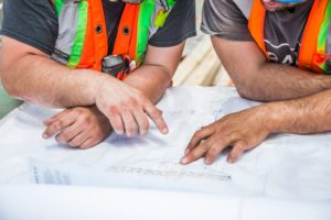 Two construction workers reviewing a blueprint together