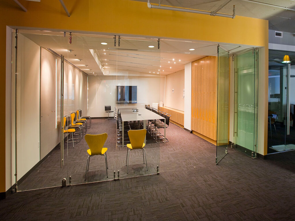 The HNTB headquarters. An office meeting room with yellow and brown chairs, a yellow wall, and a foldable glass wall divider.