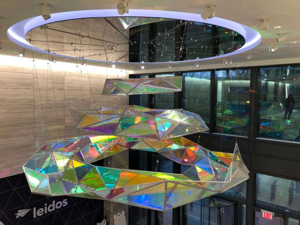 An art piece at the Reston Town Center in front of Leidos. A large mirror sits on the ceiling with various circular crystals hanging below.