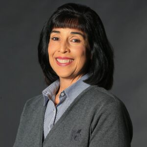 Cindy French, one of KGa's Women in Construction. Our Vice President of Human Resources. A tan woman with dark black hair, a button up shirt, and grey sweater.