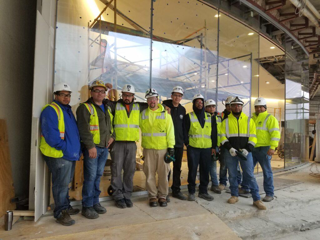 An image of Kensington Glass Arts Orange Team (including Elmer Melendez) at the 600 New Hampshire Avenue job site.