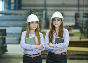 An image of two women in construction. They are wearing purple collared shirts, black pants, and white hard hats.