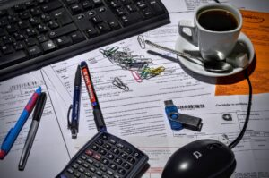 Image of a desk at Kensington Glass Arts that may be used by Mike Corcoran. The desk features a keyboard, mouse, pens, papers, paper clips, a calculator, a flash drive, and a coffee mug.